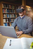 Mature student in virtual reality headset using laptop. To help with studying at college library Royalty Free Stock Photography