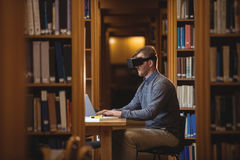 Mature student in virtual reality headset using laptop. To help with studying at college library Royalty Free Stock Photos