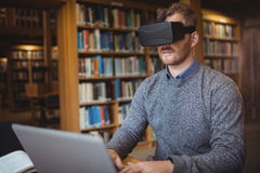 Mature student in virtual reality headset using laptop. To help with studying at college library Stock Photo