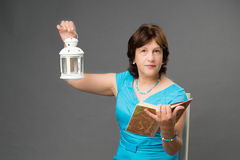 Mature student woman with book and lantern Royalty Free Stock Photography
