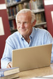 Mature student working in library Stock Image