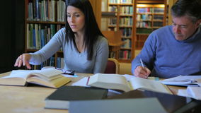 Mature students doing assignment in library stock video footage