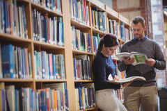 Mature students reading a book. In college library Royalty Free Stock Images