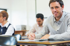 Mature students taking notes in classroom Stock Photos