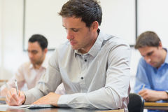Mature students taking notes in lecture Stock Photos
