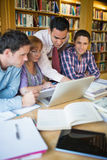 Mature students with teacher and laptop in library Stock Photo