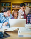 Mature students with teacher and laptop in library Royalty Free Stock Image