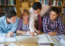Mature students with teacher and laptop in library Stock Photography