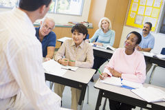 Mature students and their teacher in a classroom Royalty Free Stock Photos
