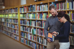 Mature students using digital tablet. In college library Royalty Free Stock Image