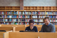Mature students using laptop to help with studying. In college library Stock Photo