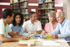 Mature students working in library stock images