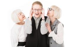 Mature stylish businesswoman shutting ears between two senior businesswomen in eyeglasses. Isolated on white stock images