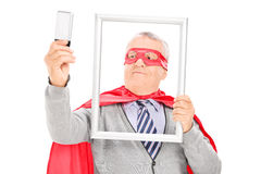 Mature superhero taking a selfie with picture frame Royalty Free Stock Image
