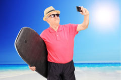 Mature surfer taking a selfie with cell phone. Mature surfer taking a picture of himself with cell phone at the beach Royalty Free Stock Images
