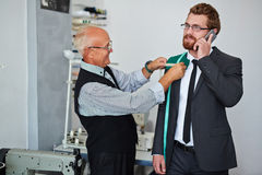 Mature tailor measuring client Stock Images