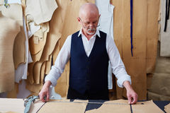 Mature tailor at work. Mature tailor working with patterns and measuring tape royalty free stock photography