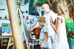 Mature Teacher Helping Kids in Art Studio. Side view portrait of mature art teacher teaching children painting in art class explaining techniques and pointing at royalty free stock image