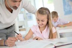 Mature teacher helpping a pupil Stock Images
