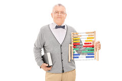 Mature teacher holding a book and an abacus Stock Photos