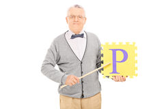 Mature teacher holding a piece of puzzle Royalty Free Stock Photos
