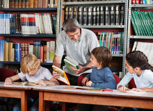 Mature Teacher Showing Book To Schoolboy In Stock Images