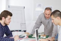 Mature teacher and students in computer lab classroom royalty free stock photography