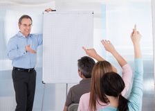 Mature teacher teaching students Stock Photo