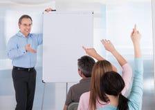 Mature teacher teaching students. Happy Mature Male Teacher Teaching Student In Classroom Stock Photo