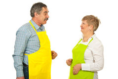 Mature team of chefs talking. Mature team of chefs in yellow and green aprons having conversation isolated on white background Stock Photos
