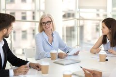 Mature team leader sitting with colleagues at briefing. Workers headed by team leader mature female gathered together in conference room discussing business royalty free stock images