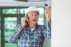 Mature technician installing cctv and talking on phone. Mature technician installing cctv and talking on the phone Stock Photos