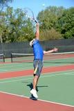 Mature tennis player during a match. Mature tennis player serving during a match on a sunny day Stock Photography