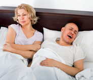 Mature tired evil girl looking at snoring boyfriend Stock Photos