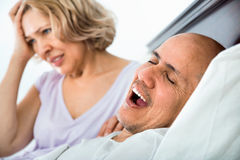 Mature tired girl looking at snoring boyfriend Stock Photography