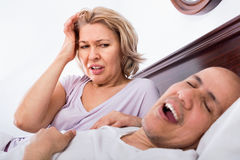 Mature tired girlfriend cannot stand guy snoring loudly. Mature tired angry girlfriend cannot stand guy snoring loudly in sleep Stock Photos