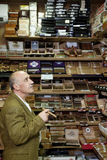 Mature tobacco shop owner looking at cigars on display Royalty Free Stock Photos