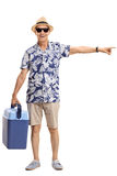 Mature tourist with a cooling box pointing right. Full length portrait of a mature tourist with a cooling box pointing right isolated on white background Royalty Free Stock Photo
