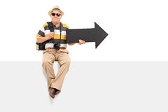 Mature tourist holding an arrow seated on panel Royalty Free Stock Images
