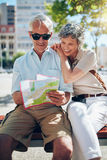 Mature tourist reading city map royalty free stock photography