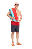 Mature tourist in swim trunks holding a towel Stock Photo