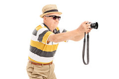 Mature tourist taking a picture with camera Royalty Free Stock Photos