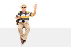 Mature tourist waving with his hand. Seated on a billboard isolated on white background Stock Photography