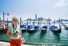 Mature tourist woman stays against row of gondolas Stock Photos