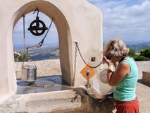 Mature tourist woman drinks fresh water from old draw well royalty free stock images
