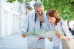 Serious mature tourists walking trough the town, looking at the map to find directions royalty free stock image