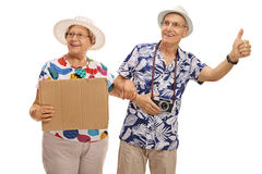 Mature tourists hitchhiking and holding cardboard sign Stock Images