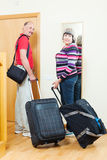 Mature  tourists with luggage near door Royalty Free Stock Image