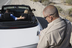 Mature Traffic Cop Writing Ticket. High angle view of a mature traffic cop writing ticket with couple sitting in the car Stock Photo
