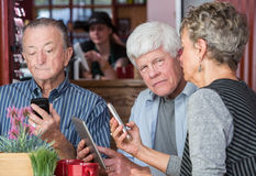 Mature Trio in Coffee House Using Electronic Devices Stock Photography